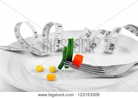 French bean, small piece of carrot and corn with measuring tape in plate closeup