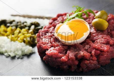 Beef tartare served with a set of ingredients on a grey surface, close up