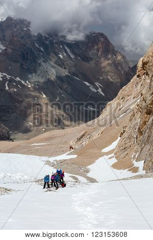 Mountain Valley Scenic View and Group of People on Snowfield Putting on Belaying Climbing Gear Vertical