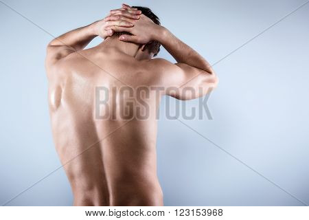 Studio shot of handsome young man with naked torso. Man suffering from neck ache