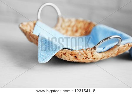 Wicker salver with blue napkin on wooden table background, closeup