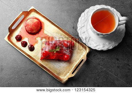 Powdered cherry strudel with mint and cup of tea on golden tray