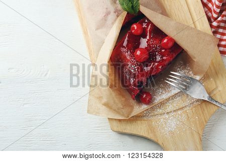Cherry strudel with mint and fork on cutting board