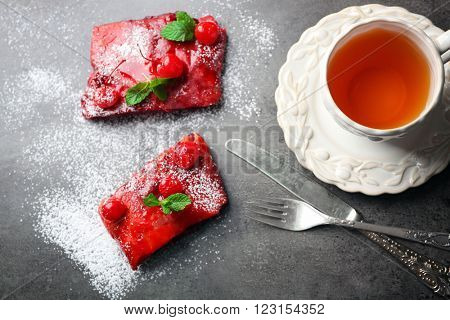 Powdered cherry strudel with mint and cup of tea