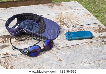 Sunglass baseball cap and mobile phone on table in hiking
