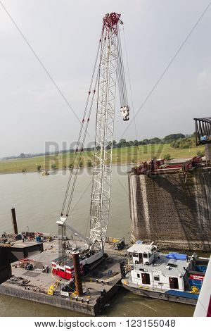 WESEL - SEPTEMBER 10: Floating crane carrying girder platform to support a bridge deconstruction on Rhine river Germany on September 10 2012