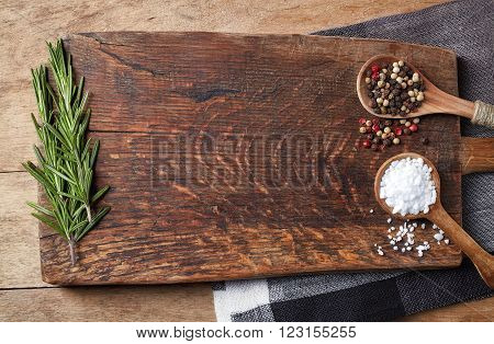 Salt pepper in wooden spoons and rosmarinus on wooden cutting board top view
