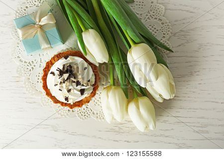 Bouquet of fresh tulips, cake and present box on wooden table, top view