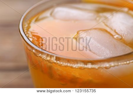 Glass of orange juice with ice block on wooden background, close up