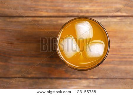 Glass of orange juice with ice block on wooden background