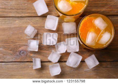 Glasses of orange juice with ice block on wooden background