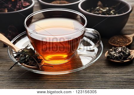 Tea concept. Different kinds of dry tea in bowls. Glass cup of tea on wooden background