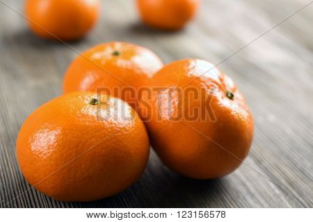 Fresh delicious unpeeled tangerines  in a heap on the wooden table, close up