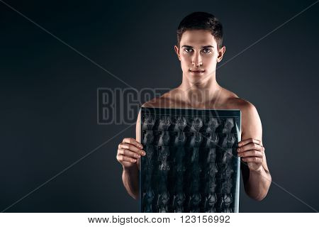 Studio shot of handsome young man with naked torso. Muscular man looking at camera and holding X-ray photo