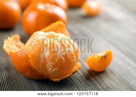 Fresh delicious peeled and unpeeled tangerines with slices on the wooden table, close up