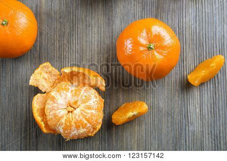 Fresh delicious  peeled and unpeeled tangerines with slices on the wooden table, top view