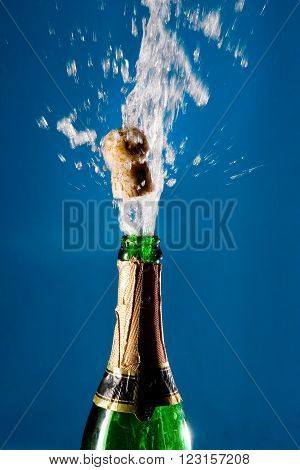 Bottle of champagne with a popping cork (against a blue background)