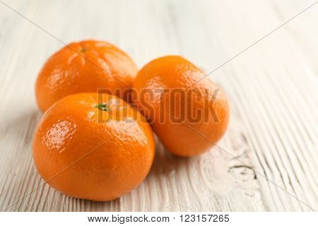 Three fresh delicious unpeeled tangerines on the white wooden table, close up