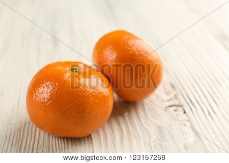 Two fresh delicious unpeeled tangerines  on the white wooden table, close up