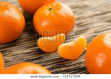 Fresh, delicious unpeeled tangerines, with slices on the stripped material, close up