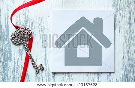 house icon and the keys on turquoise wooden background the symbol for construction loan mortgage property or home excellent for a house to buy sell rent business ideas announcements