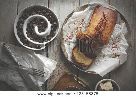 Composition of tasty cake with chocolate morsels on grey wooden table background, top view