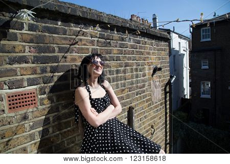 Girl in black polka dot dress and sunglasses sitting on the balcony of the second floor of a house in London. She takes sun baths in the early spring.