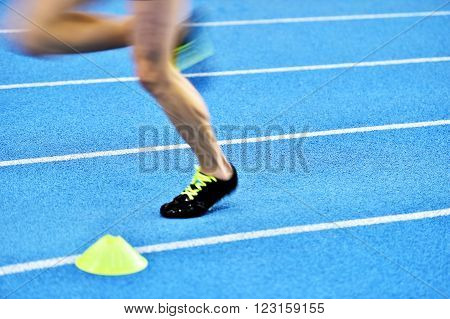 Blurred athlete by a slow camera shutter speed competing on blue sprint track