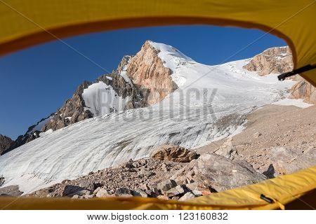 Glacier and High Mountain Peak Taken throw Window Entrance Door of Alpine Tent Blue Sky Rocky Moraine