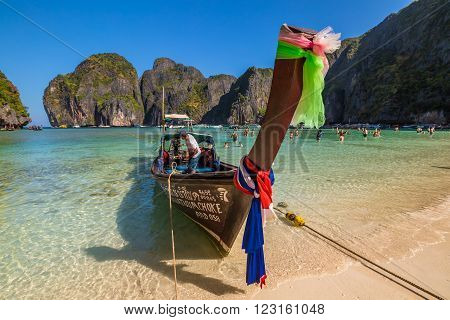 Maya Bay, Phi Phi Leh, Thailand - December 31, 2015:  a long tail boat, typical traditional wooden boat, near the shore of Maya Bay lagoon of famous movie The Beach with Leonardo Di Caprio.