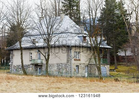 ZAKOPANE, POLAND - MARCH 09, 2016, Brick villa is a dwelling house built in the first quarter of the 20th century, stone foundation and sloping roofs refer to the architectural style of the region
