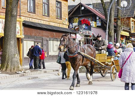 ZAKOPANE POLAND - MARCH 06 2016: Coachman is carrying tourists along Krupowki street in main shopping area and pedestrian promenade in the city center of Zakopane