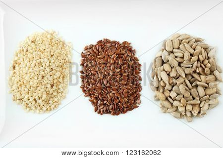 Sesame, flax and sunflower seed in plate on wooden table