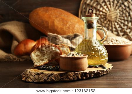 Composition of sunflower seeds, bread and oil on wooden table background, closeup