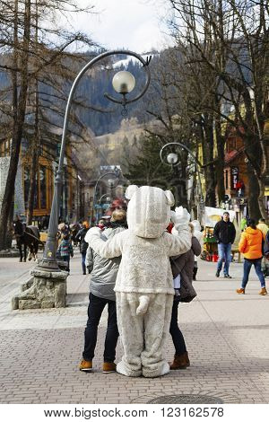 ZAKOPANE POLAND - MARCH 09 2016: Unidentified man portrays the role of a teddy bear tourists eagerly wants to have photos with him. It is an attraction on the famous street Krupowki