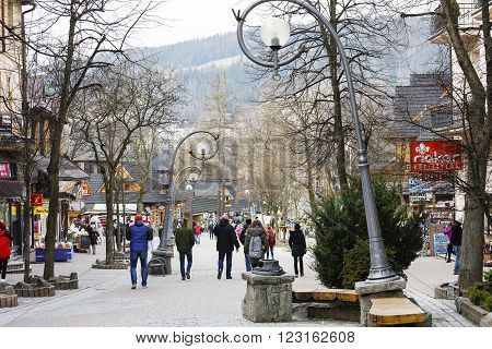 ZAKOPANE POLAND - MARCH 09 2016: Unidentified people walk along Krupowki Street. It is main shopping area and pedestrian promenade in the downtown is very famous and frequently visited by tourists