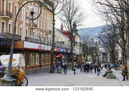 ZAKOPANE POLAND - MARCH 09 2016: Unknown passers are walking along Krupowki Str. It is main shopping area and pedestrian promenade in the downtown is very famous and frequently visited by tourists