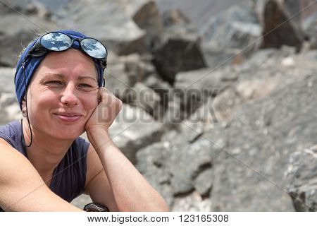 Portrait of Female Alpine Climber Smiling and Merry with Head Band and Sunglasses with Sky Reflection