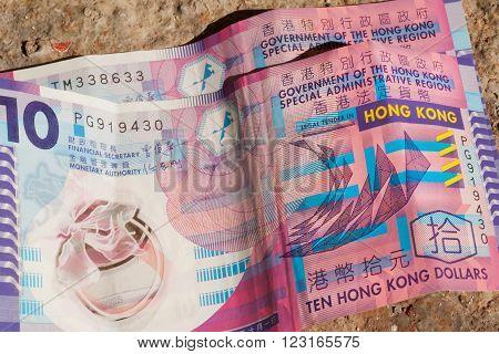 Few crumpled bills of Hong Kong dollar on ground. Government finance bank ten dollars.