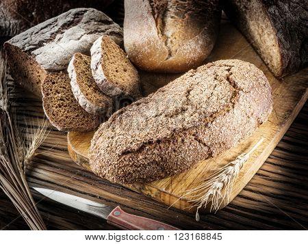 Black bread loafs on the wooden plank.
