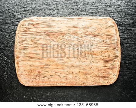 Empty chopping wooden board on the graphite background.