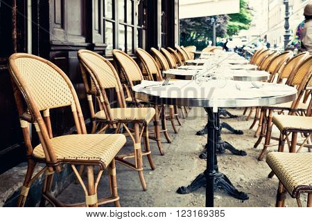 Street view of a coffee terrace with tables and chairs in europe.