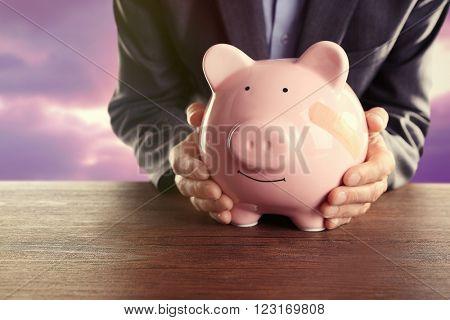 Man holding Piggy Bank with adhesive bandage, on sunset background