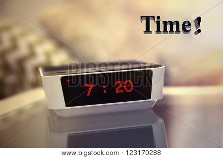 Digital clock showing 7:20 o'clock on a bedside table in bedroom