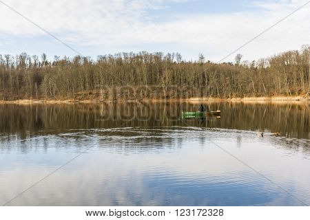 Otomin Poland - March 23 2016: Angler in a boat on the lake of the woods.