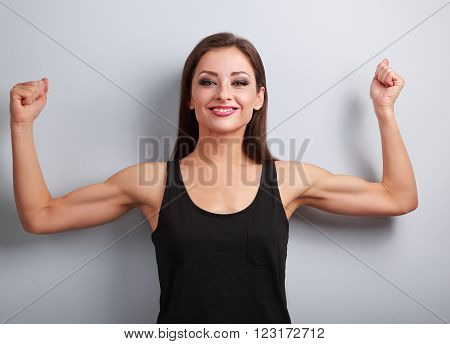 Pleased Strong Fit Woman Showing Muscle Biceps With Happy Smiling On Blue Background