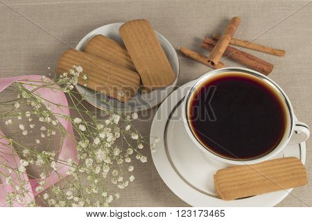 A hot Cup of coffee cinammon cookies on a linen napkin with sprigs of baby's breath and pink ribbon