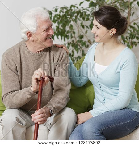 Old man holding a cane and smiling to his granddaughter