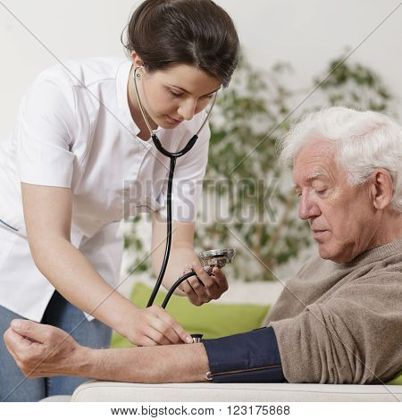 Young female nurse with stethoscope taking blood pressure