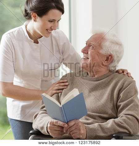Elderly man reading book with his nurse